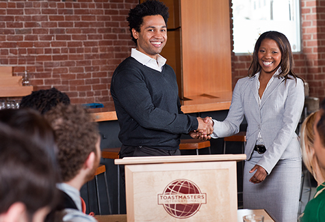 Man and woman shaking hands at a lectern.  The lectern has a Toastmaster logo on the front